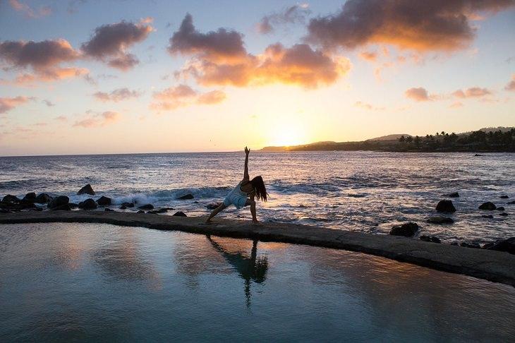 תנוחות יוגה לחיזוק המערכת החיסונית: אישה עושה יוגה על החוף מול השקיעה