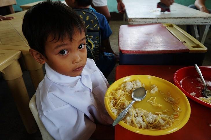 איך למזער תסמינים של הפרעות קשב וריכוז עם תזונה: ילד יושב מול צלחת עם אוכל ומביט למצלמה