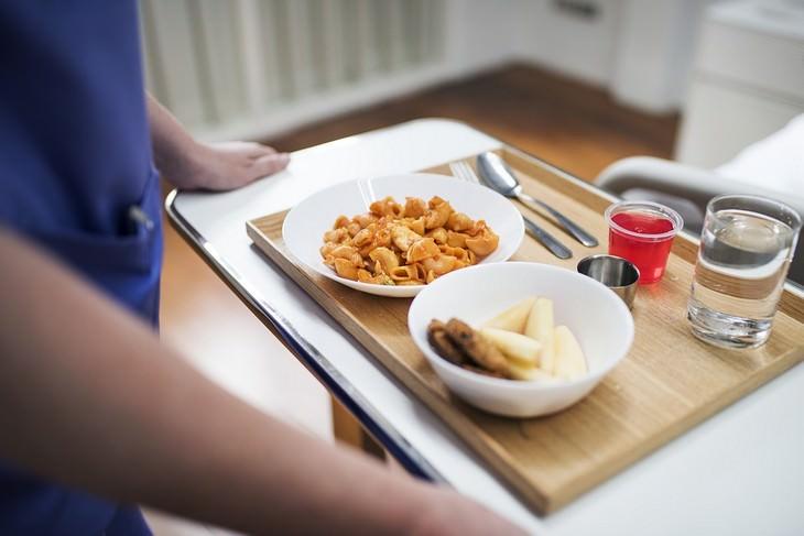 אנטיביוטיקה והמאכלים שיש לאכול בעת נטילתה ואחריה: ידיים אוחזות במגש עם כוס מים וצלחות עם אוכל