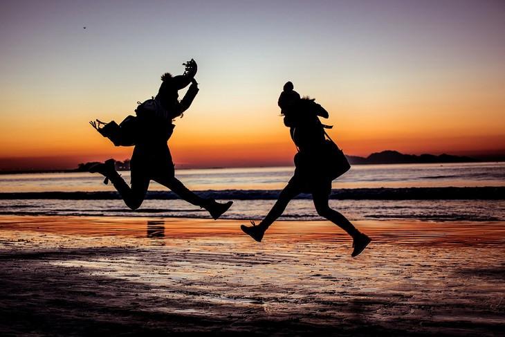 יצירת מערכת יחסים ארוכת שנים: שתי נשים קופצות על חוף הים