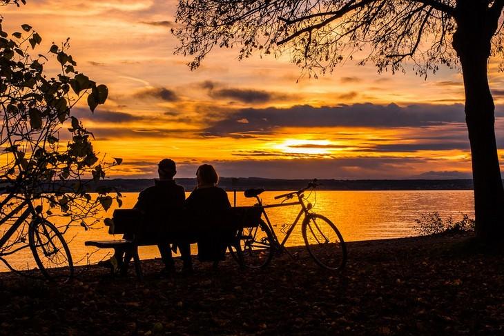 יצירת מערכת יחסים ארוכת שנים: זוג יושב בספסל מול שקיעה