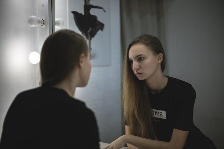 ממנה נובעת ביקורת עצמית וכיצד להפסיק אותה: אישה מדוכדכת עומדת מול מראה
