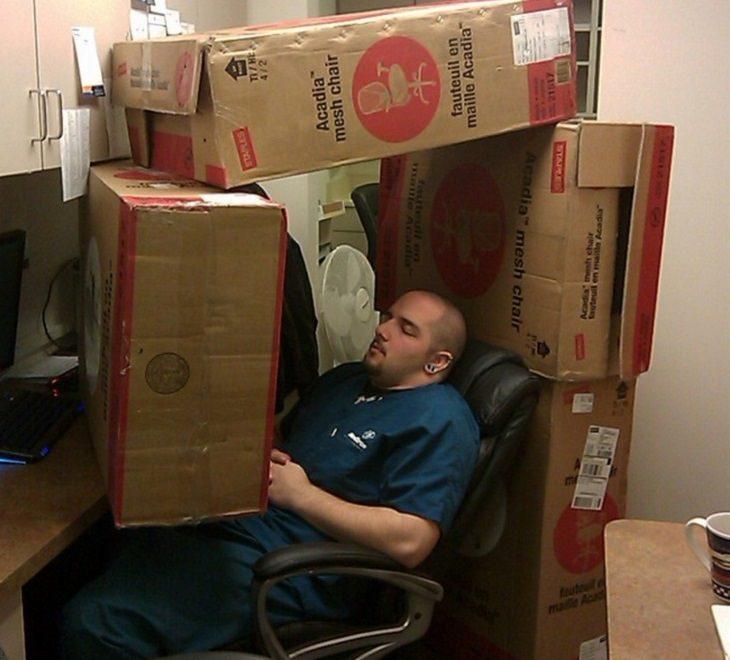 תמונות של אנשים שנרדמו במקומות משונים: גבר ישן על כיסא כשסביבו קרטונים גדולים
