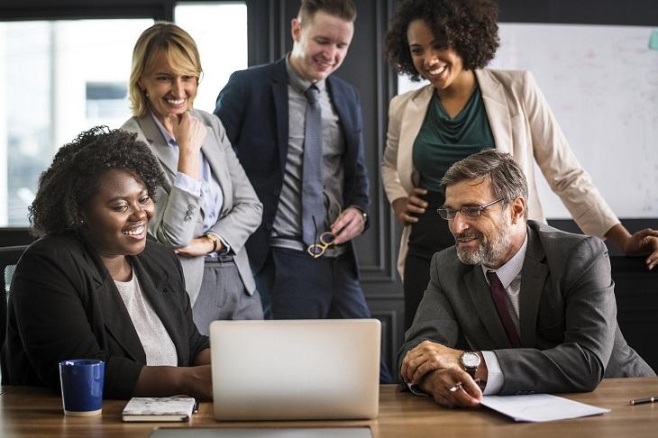 טיפים לפאוור פוינט: אנשים במשרד יושבים סביב מחשב ומביטים במסך מחוייכים
