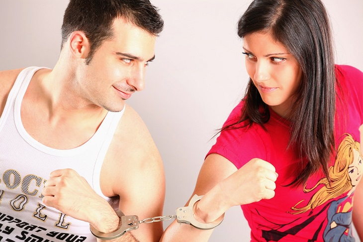עצות לתחזוק הזוגיות: זוג כבול זה לזה באזיקים, האשה והגבר מביטים אחד על השני בחצי חיוך