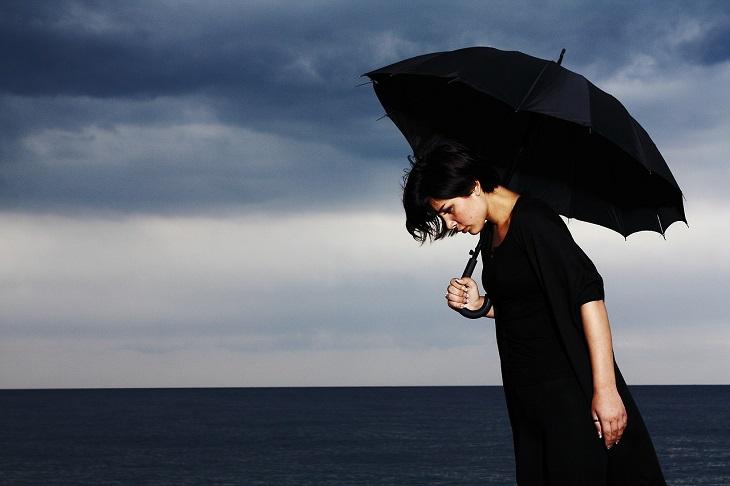 תסמינים לגידול סרטני במוח: אישה עומדת על שפת הים בבגדים שחורים ומחזיקה מטריה שחורה, פניה מדוכאים