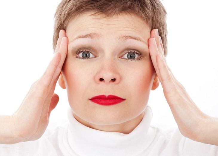 מאכלים הגורמים למיגרנות: אישה מחזיקה ברקות ראשה עם בכפות ידיה