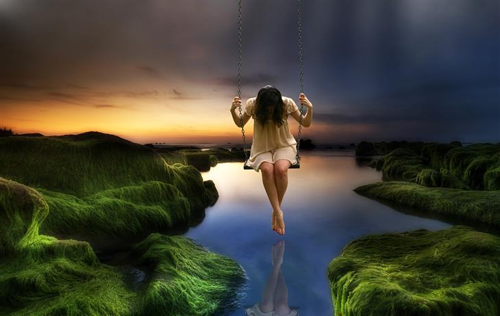 זיהוי דיכאון לפי השפה שבה משתמשים: אישה מתנדנדת על נדנדה מעל לאגם וראשה שמוט
