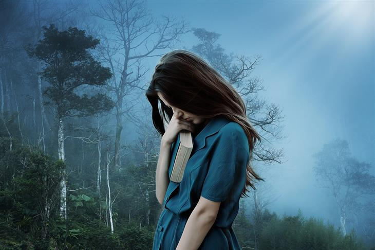 זיהוי דיכאון לפי השפה שבה משתמשים: אישה אוחזת ספר צמוד לראשה ומתבוננת מטה, כשמאחוריה יער