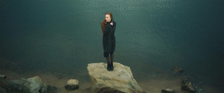 זיהוי דיכאון לפי השפה שבה משתמשים: אישה עומדת על סלע בחוף ים