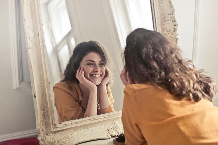 התנהגויות אנוכיות חיוביות: אישה מסתכלת על עצמה במראה ומחייכת
