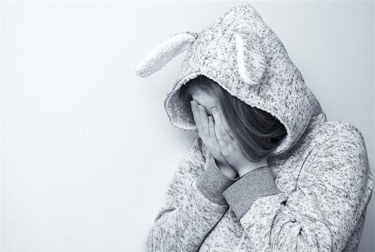 ללמד את הילדים לעמוד בפני לחץ חברתי: נערה עם קפוצ'ון עם אוזני ארנב, אוחזת את פניה בידייה