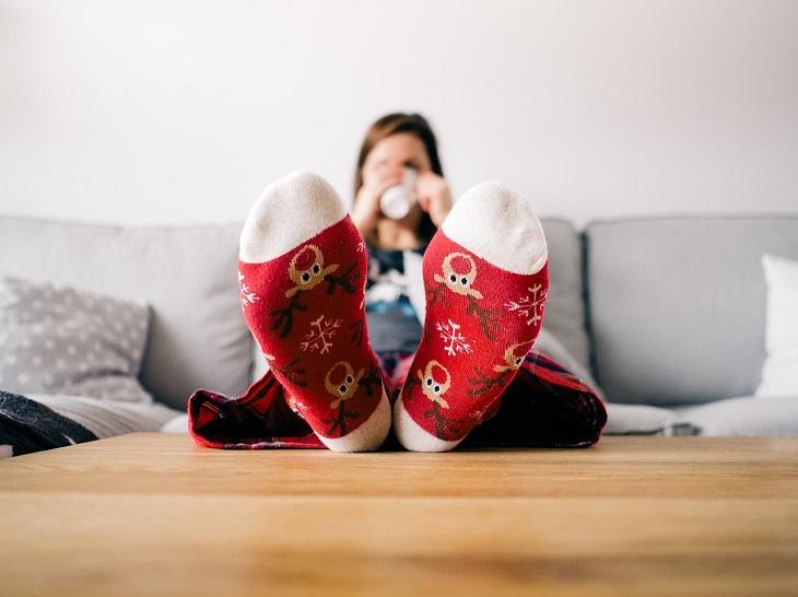 התנהגויות אנוכיות חיוביות: אישה יושבת על הספה, שותה קפה ומרימה את רגליה על השולחן
