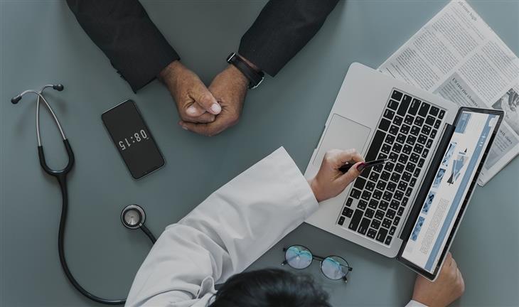 תותב לפין: ידיים של רופא ומטופל מעל לשולחן הרופא, כשהרופא מצביע על מסך מחשב נייד