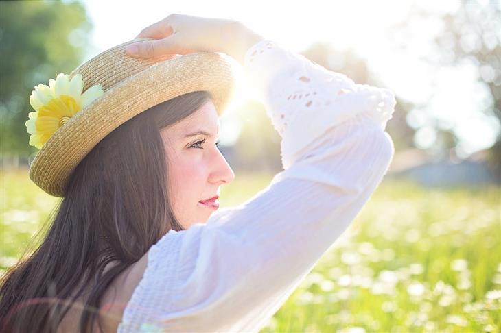 טעויות בדיאטה: אישה יושבת בשדה פרחוני ואוחזת בכובע שעל ראשה