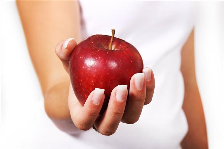 טעויות בדיאטה: יד של אישה מחזיקה תפוח
