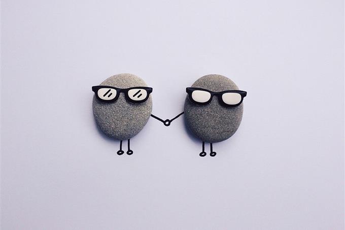בחן את עצמך: שני חלוקי נחל עם משקפי שמש וציור בעט של ידיים אוחזות אחת בשנייה