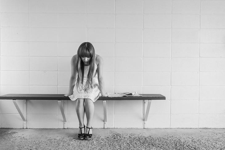 סיבות נסתרות לדיכאון: אישה יושבת על ספסל וראשה מופנה כלפי מטה