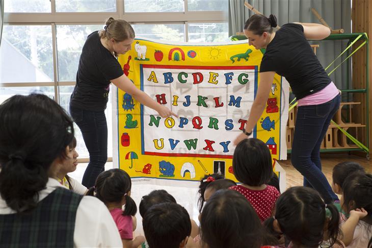 מיתוסים על גידול ילדים דו לשוניים: שתי נשים מרימות שלט צבעוני ועליו אותיות ה-ABC