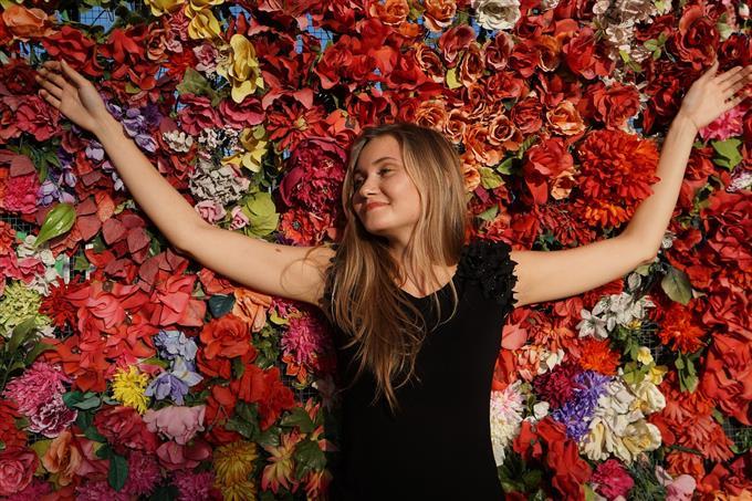 בחן את עצמך: אישה פורשת ידיים לצדדים מול קיר פרחים