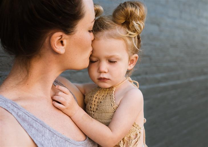 איך להפסיק לצעוק על הילדים: אמא מנשקת את בתה