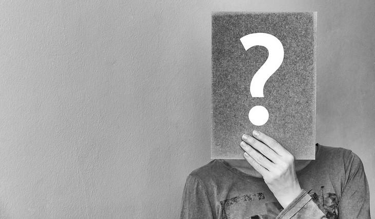שאלות לחיזוק היחסים במשפחה: אישה מחזיקה מול פניה ספר שעליו סימן שאלה