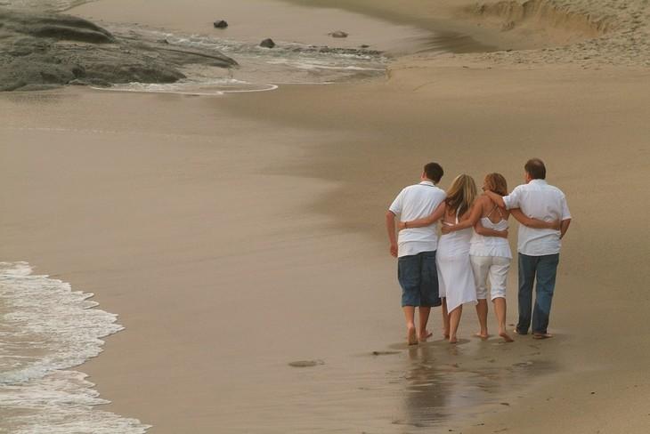 שאלות לחיזוק היחסים במשפחה: ארבעה בני משפחה הולכים מחובקים על חוף הים