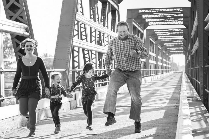 שאלות לחיזוק היחסים במשפחה: זוג הורים ושני ילדים הולכים יד ביד ומדלגים