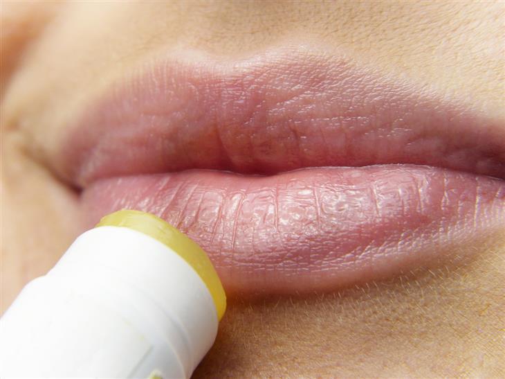 הקשר בין הרפס לאלצהיימר: אישה מורחת שפתון על שפתיה