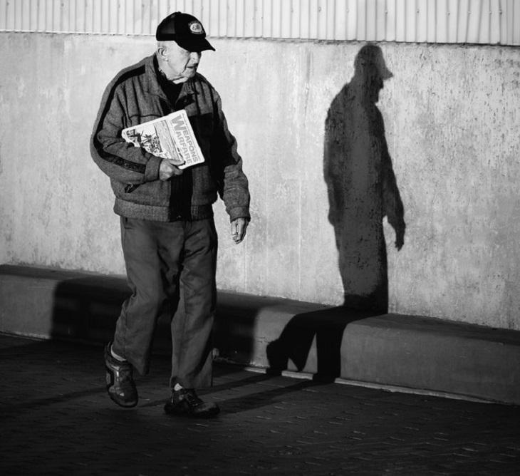8 סוגי הפרעות נפש: איש מבוגר עם עיתון ביד הולך לבדו ברחוב כשעל הקיר הצל שלו