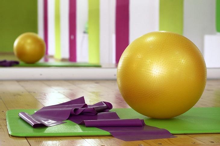 תרגילים לחיטוב הירכיים הפנימיות: כדור אימון מונח על מזרן ולידו רצועה