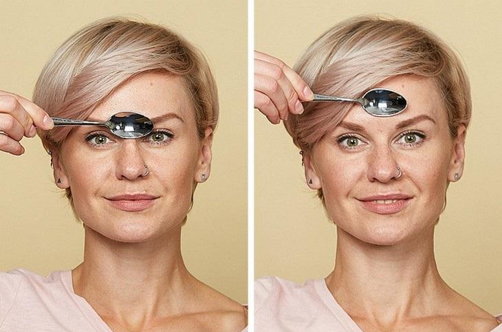 עיסוי עור הפנים בעזרת כפיות ומים: אישה המדגימה עיסוי שיעזור להפחית את הקמטים בין הגבות