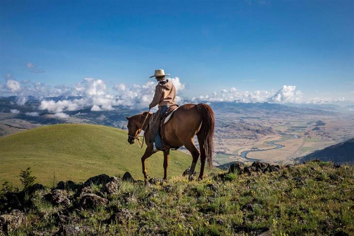 תמונות היום של נשיונל ג'אוגרפיק: עובדת החווה, הילארי אנדרסון, רוכבת על סוס באזור הפארק הלאומי ילוסטון, ארצות הברית. צולם על ידי: Cory Richards.