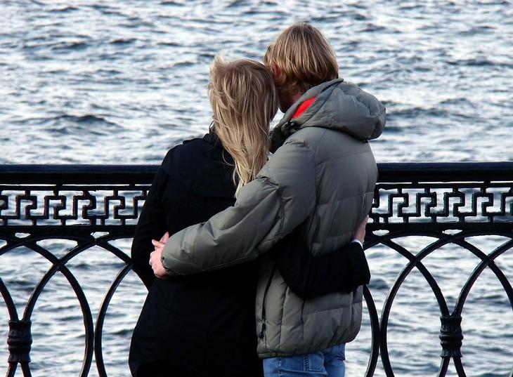איך להרגיש ביטחון רגשי בזוגיות: זוג מחובק עומד על שפת הים