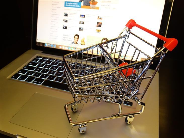 מיסים ומכסים בהזמנות מוצרים מקוונות:עגלת קניות קטנה על מחשב נייד