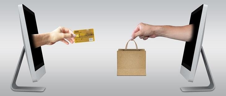 מיסים ומכסים בהזמנות מוצרים מקוונות: יד יוצאת ממסך מחשב ומעבירה שקית אל יד ממסך מחשב שני שאוחזת בכרטיס אשראי