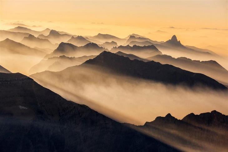תמונות היום של נשיונל ג'אוגרפיק: פסגותיהם של הרי הרוקי הצפוניים מלאי עשן בשעות הבוקר בפארק הלאומי גליישר, ארצות הברית. צולם על ידי: Keith Ladzinski.