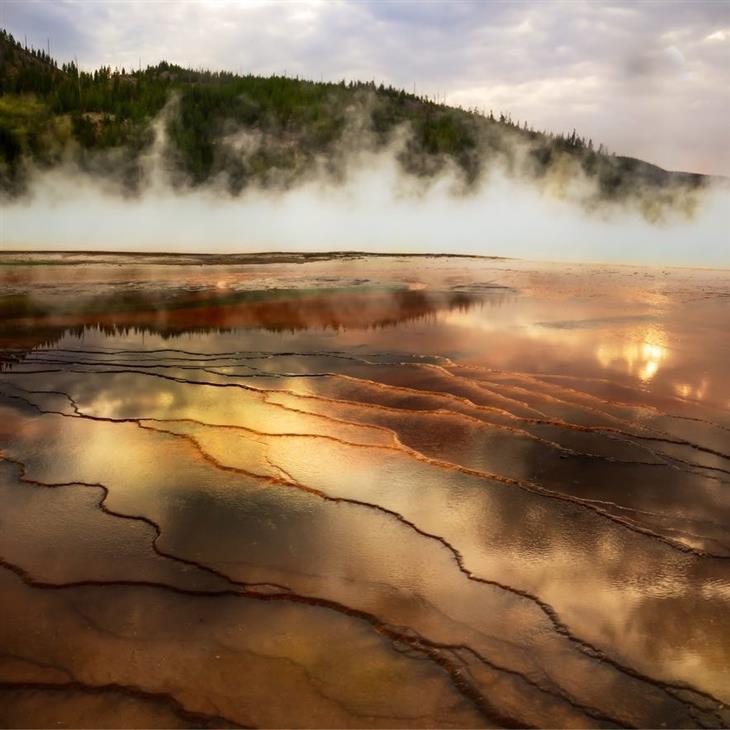 תמונות טבע מדהימות: אגם מחורץ שמעליו אדים, ומאחוריו הר ושמים