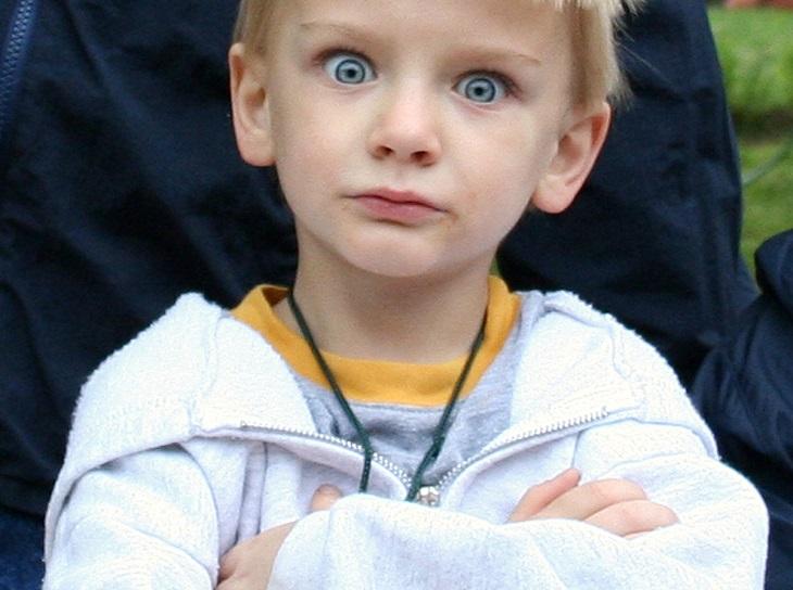 עצות להתמודדות עם ילד עקשן: ילד משלב ידיים ועושה פרצוף למצלמה