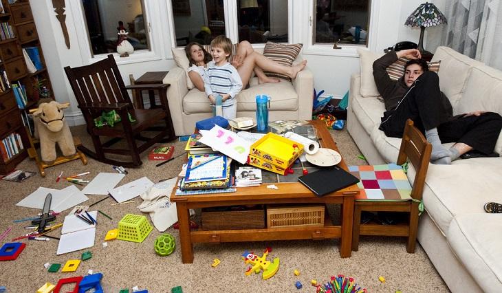 כיצד לגרום לילדים להיות מעורבים במטלות הבית: ילדים יושבים על הספה כשהחדר מסביבם מבולגן לחלוטין