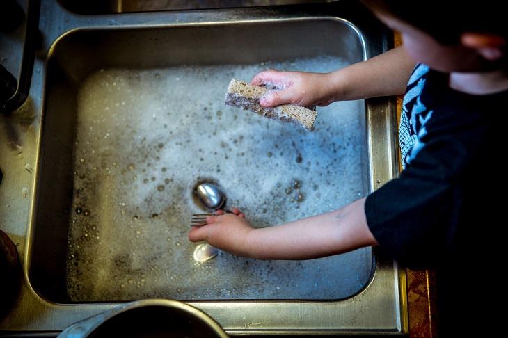 כיצד לגרום לילדים להיות מעורבים במטלות הבית: ילד רוחץ כלים
