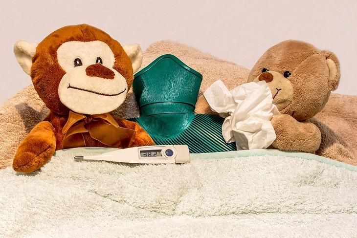 טיפים להורים למנוע הצטננות: בובות במיטה עם מד חום וכרית חימום