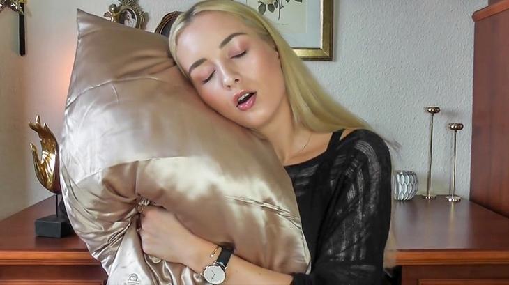 טיפים לשמירה על מראה צעיר: אישה מצמידה כרית סאטן לראשה