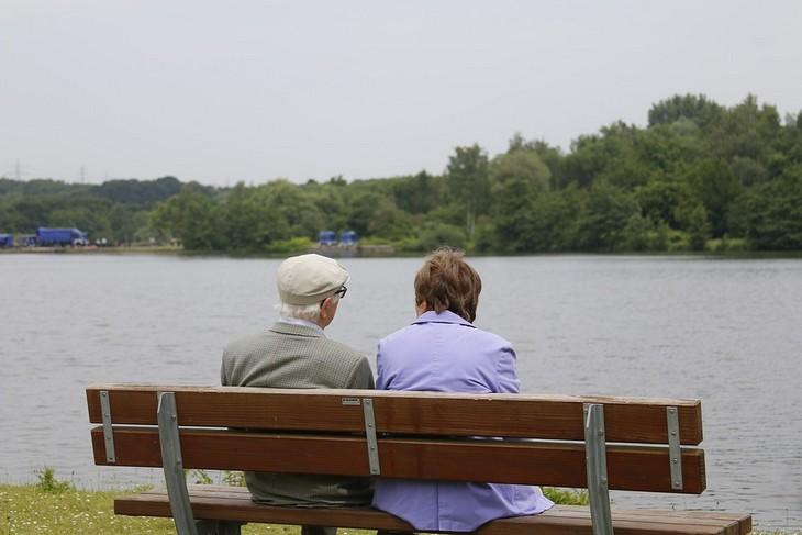 עצות לזוגיות מאושרת: זוג מבוגרים יושבים על ספסל מול אגם