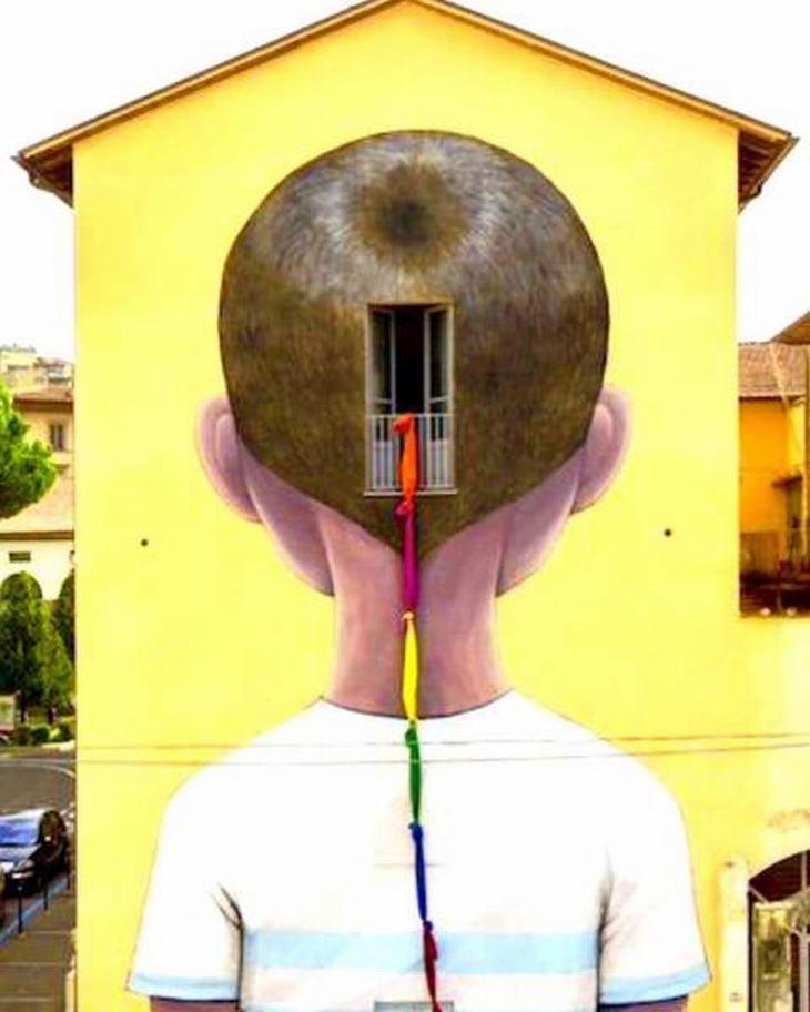 יצירות אמנות רחוב: ציור קיר של ילד מאחור, כשצמת בד משתלשלת מחלון הממוקם באחורי ראשו