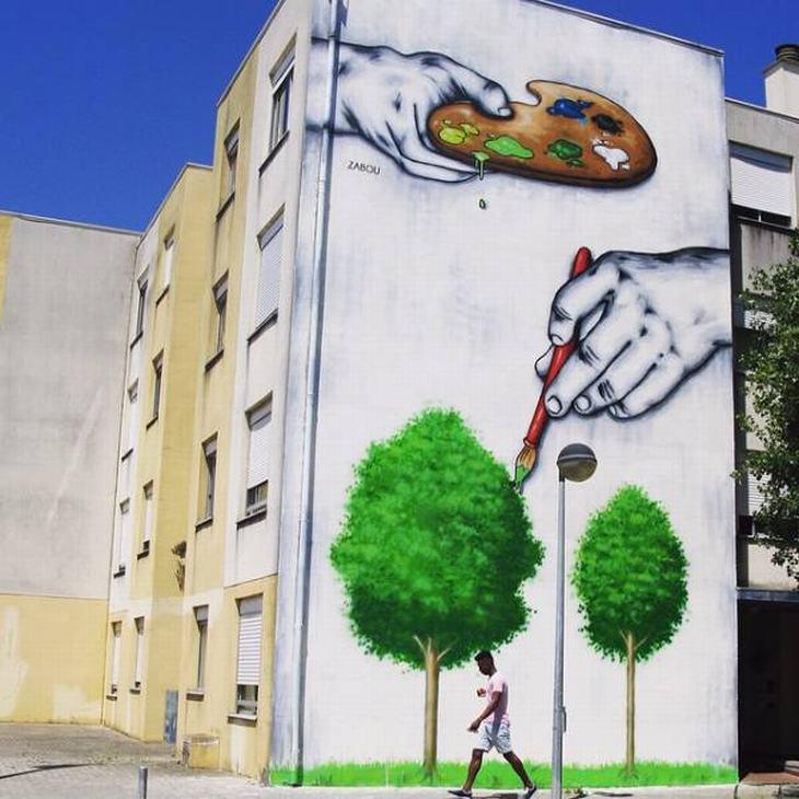 יצירות אמנות רחוב: ציור קיר של ידיים האוחזות בפלטת צבעים ומציירות עץ