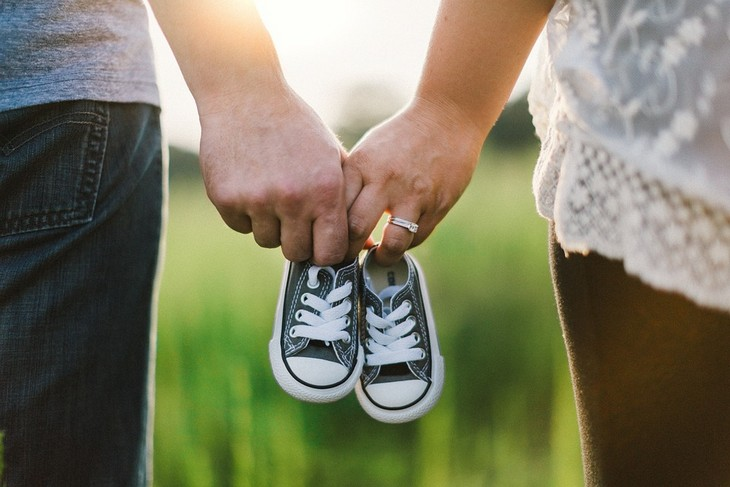 בעיות בנישואים: גבר ואישה מחזיקים יחדיו זוג נעלי תינוק
