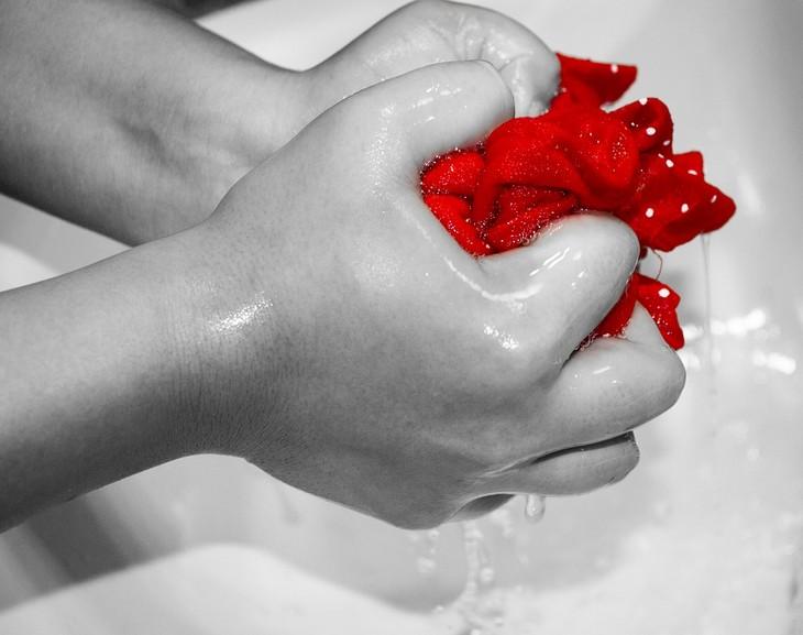 הסרת כתמי דאודורנט: שתי ידיים סוחטות בגד אדום
