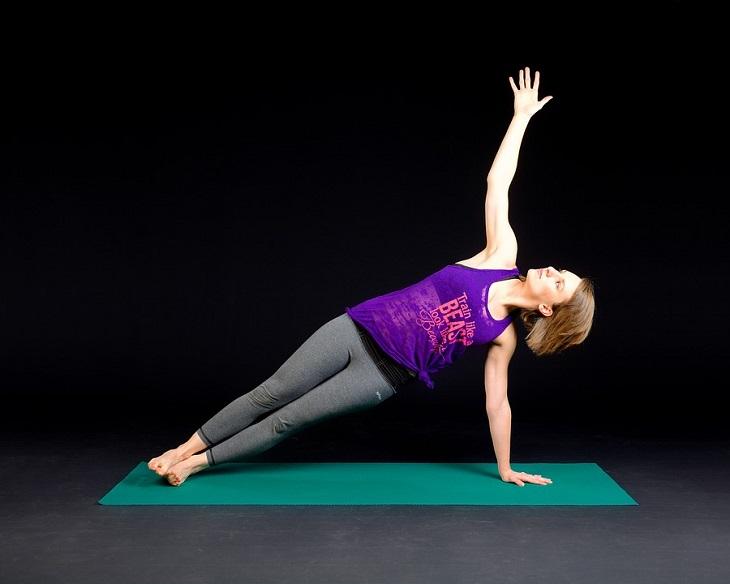תרגילים ויתרונות לחיזוק שרירי הליבה: אישה מבצעת תרגיל פלאנק על מזרן
