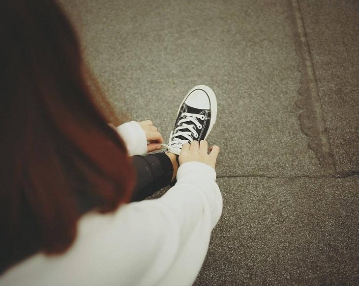 תרגילים ויתרונות לחיזוק שרירי הליבה: אישה קושרת נעליים